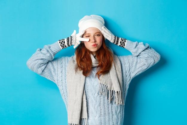 Winter- und ferienkonzept. glückliches rothaariges mädchen im mützenhut, im schal und in den handschuhen, die friedenszeichen und fältchenlippen frech zeigen, die kamera anstarren, pullover tragen und über blauem hintergrund aufwerfen.