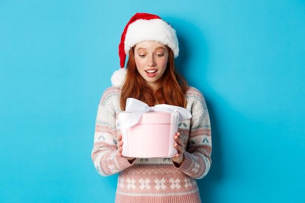 Winter- und heiligabend-konzept. berührtes und geschmeicheltes rothaariges mädchen, das box mit weihnachtsgeschenk anschaut, erstaunt lächelt und in weihnachtsmütze vor blauem hintergrund steht