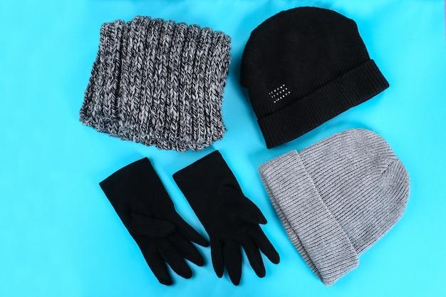 Winter- und herbstkleidung, hüte, schals, handschuhe auf einem blauen pastellhintergrund.