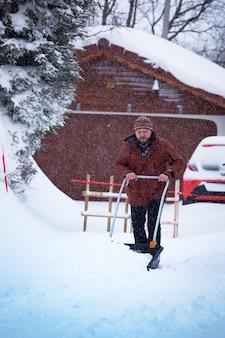 Winter und schneefall. mann reinigt schnee mit einer schaufel