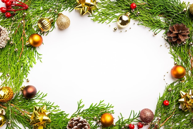 Winter- und weihnachtskranz mit goldenem weihnachtsspielzeug auf weißem hintergrund