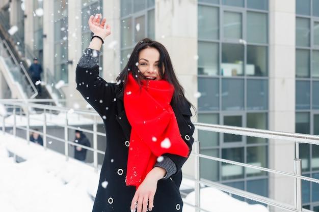 Winter, weihnachten, lifestyle, urlaub und modekonzept - hübsche junge lächelnde frau in schwarzem mantel und rotem schal, die in der winterstadt posiert. schneit