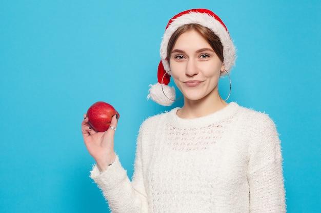 Winter, weihnachten, menschen, schönheitskonzept - hübsches blondes tragen des weihnachtshutes auf hellblauer oberfläche