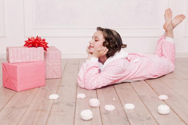 Winter, weihnachten, urlaub, süßigkeiten, geburtstag, feiern und kinderkonzept - süßer pyjama für kleine mädchen mit süßigkeiten, die auf dem boden sitzen, glückliches kindheitskonzept. mädchengeschenke, weicher hund, seifenblasen.