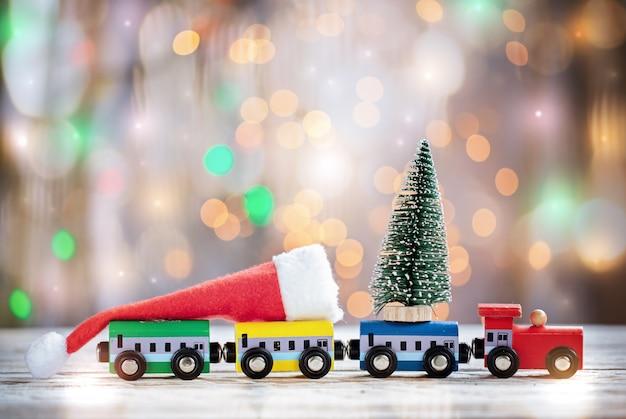 Winter-weihnachtshintergrund bunter miniaturzug mit tannenbaum. feiertagsgrußkarte