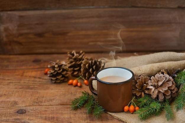 Winter, weihnachtshintergrund im rustikalen stil. ein vintage-metallbecher mit heißem milchtee steht auf einer tischdecke, auf einer holzoberfläche zwischen tannenzapfen, fichtenzweigen und hagebutten. platz kopieren, flach legen