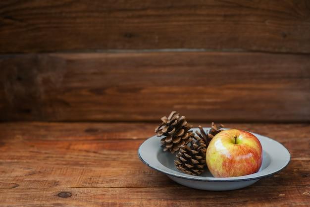 Winter, weihnachtshintergrund im rustikalen stil. eine vintage metallschüssel mit einem apfel und tannenzapfen