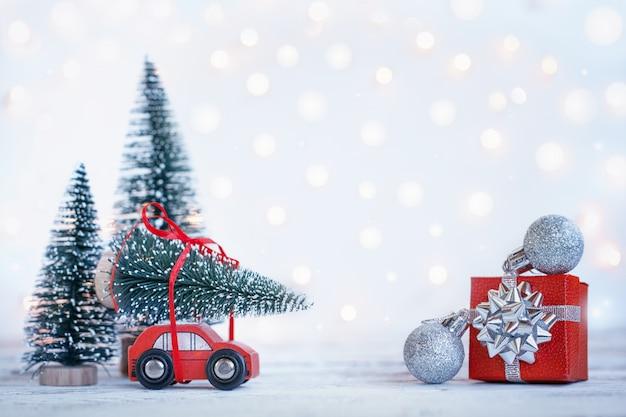 Winter-weihnachtshintergrund rotes miniaturauto mit tannenbaum. feiertagsgrußkarte.