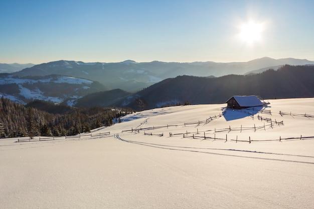 Winter-weihnachtslandschaft des gebirgstales am eisigen sonnigen tag. alte hölzerne verlassene schäferhütte im weißen tiefen sauberen schnee, waldiger dunkler gebirgsrücken, heller sonnenschein auf blauem himmel