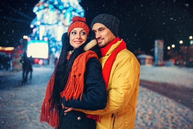 Winterabend des liebespaares im freien, feiertagsbeleuchtung. mann und frau, die romantisches treffen auf stadtstraße mit lichtern haben