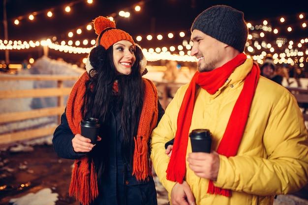 Winterabend, liebespaar geht mit kaffee im freien, feiertagsbeleuchtung auf hintergrund. mann und frau, die romantisches treffen auf stadtstraße mit lichtern haben
