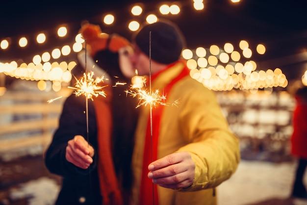 Winterabend, liebespaar mit wunderkerzen, die sich im freien küssen. mann und frau, die romantisches treffen auf stadtstraße mit lichtern haben