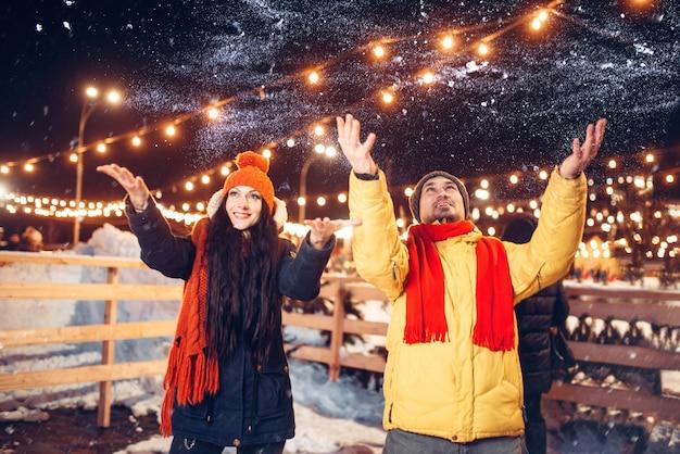 Winterabend, verspieltes liebespaar wirft schnee hoch. mann und frau, die romantisches treffen auf stadtstraße mit lichtern haben