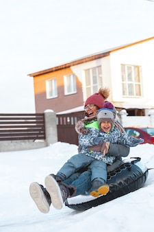Winteraktivität für mutter und kind der familie, rutsche vom schneehügel