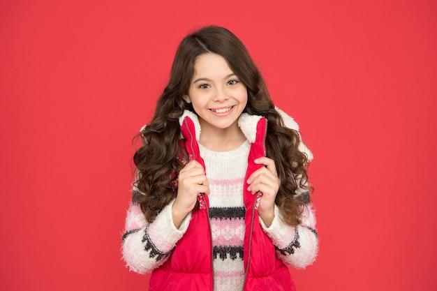 Winteraktivitäten. winter kindermode. kind mit langen lockigen haaren in weihnachtskleidung. aktivitätsstil der kalten jahreszeit. kindheitsglück. thermokleidung. glückliches jugendlich mädchen tragen warme kleidung.