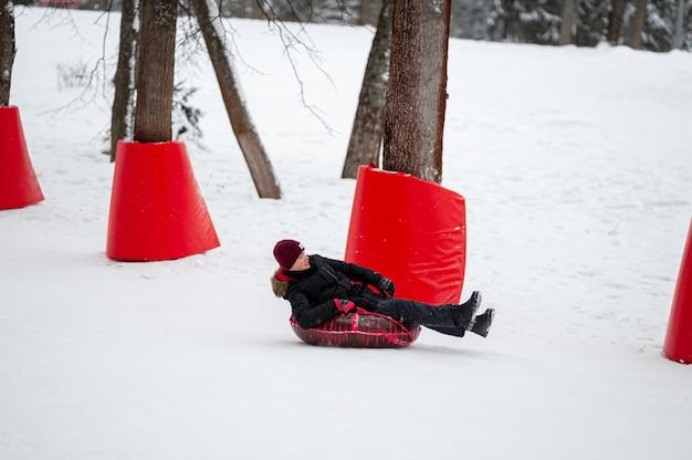 Winteraktivitätsschlauch ein teenager rollt auf einem roten schlauch an einem speziell ausgestatteten sicheren berghang