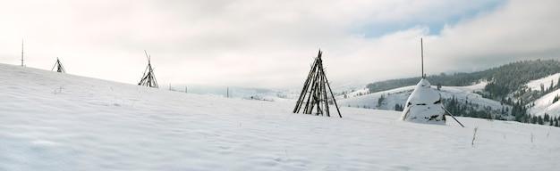 Winterbergpanorama mit heuhaufen an vorderster front (slavske village, region lviv, ukraine). sieben schüsse stichbild.