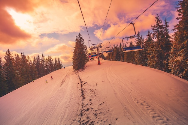 Winterbergpanorama mit skipisten und skiliften an einem bewölkten tag. weiches licht des sonnenuntergangs mit dramatischem orangefarbenem himmel. vintage toning-effekt. bukovel, karpaten, ukraine, europa