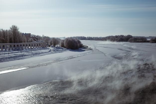 Winterblick auf den fluss mit eisigen rändern und schneebedeckten ufern im winter schöne seitenansicht