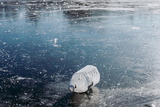 Wintereisstruktur mit rissen. müll in der natur. plastik in einem zugefrorenen see