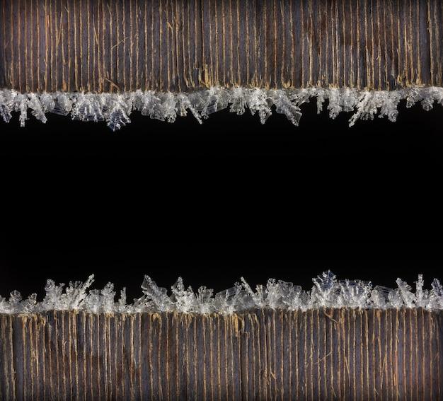 Winterfeiertag weihnachten neujahr hintergrundrahmen von makrofoto frost auf alten holzbrettern mit schwarzem raum für text