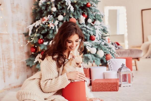 Winterferien dekoration. warme farben. bezaubernde brunettefrau in der beige strickjacke