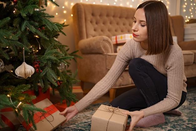 Winterferien, feier und personenkonzept - nahaufnahme der frau, die geschenk unter weihnachtsbaum setzt