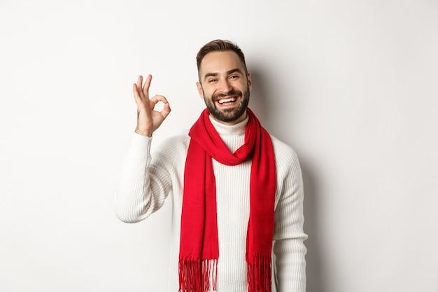 Winterferien und einkaufskonzept. zufriedener bärtiger mann, der lacht und ein gutes zeichen zeigt, genehmigt und wie das produkt, steht in weihnachtsschal und pullover, weißer hintergrund