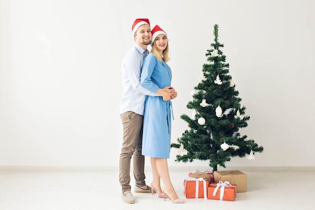 Winterferien und familienkonzept - glückliches junges paar in der nähe des weihnachtsbaums zu hause.
