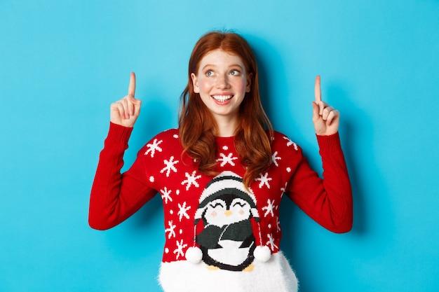 Winterferien und feierkonzept. fröhliches teenager-mädchen mit roten haaren, das logo verträumt betrachtet, mit den fingern nach oben zeigt, werbung zeigt und auf blauem hintergrund steht.