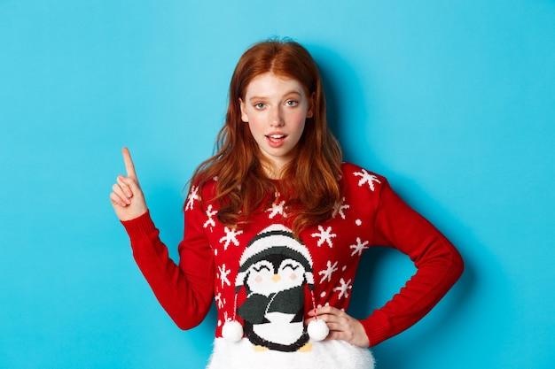 Winterferien und heiligabend-konzept. freches rothaariges mädchen im weihnachtspullover, das auf die obere linke ecke zeigt und auf die kamera starrt, auf promo-angebot hinweist, blauer hintergrund.