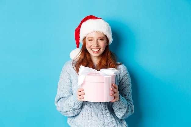Winterferien und heiligabend konzept. nettes rothaariges mädchen im pullover und in der weihnachtsmannmütze, hält neujahrsgeschenk und betrachtet kamera, die gegen blauen hintergrund stehen.