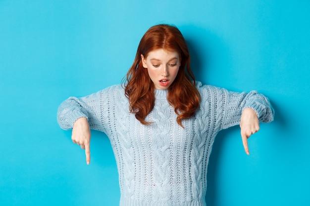 Winterferien und menschenkonzept. beeindrucktes rothaariges mädchen im pullover, das mit erstaunen schaut und nach unten zeigt und vor blauem hintergrund steht.