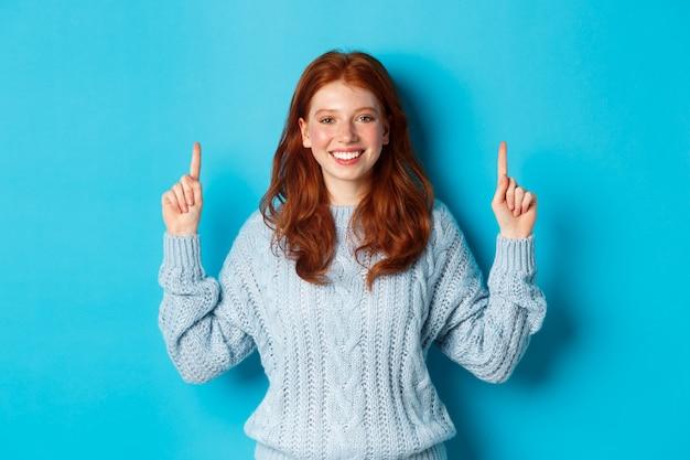 Winterferien und menschenkonzept. fröhliches rothaariges mädchen im pullover zeigt mit den fingern nach oben, zeigt logo-banner und lächelt, steht auf blauem hintergrund