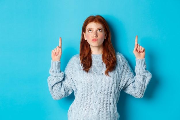 Winterferien und menschenkonzept. nachdenkliches rothaariges mädchen im pullover, das mit den fingern nach oben starrt und zeigt, zweifel hat, nachdenkt oder eine wahl trifft, auf blauem hintergrund stehend