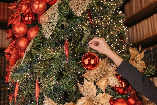 Winterferien und personenkonzept schließen oben von hand der jungen frau, die weihnachtsbaum mit rotem ball über schnee verziert