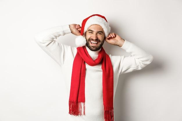 Winterferien und silvesterpartykonzept. glücklicher mann, der weihnachten feiert, weihnachtsmütze und roten schal trägt und laut lacht, weißer hintergrund