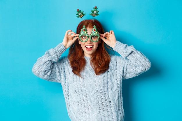 Winterferien und weihnachtsverkaufskonzept. schönes rothaariges weibliches modell, das neujahr feiert, lustiges partystirnband und eine brille trägt, albern lächelt, blauer hintergrund