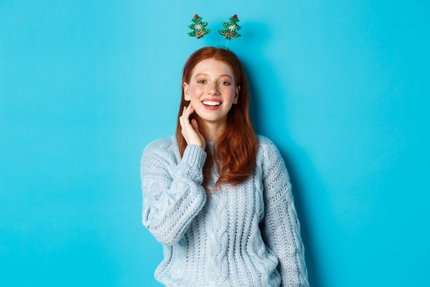 Winterferien und weihnachtsverkaufskonzept. schönes rothaariges weibliches modell feiert neues jahr, trägt lustiges partystirnband und pullover und lächelt in die kamera.