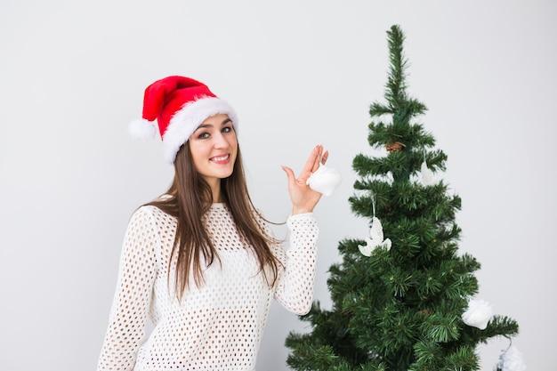 Winterferien, weihnachten und leutekonzept - porträt der schönen jungen frau in der weihnachtsmütze, die den weihnachtsbaum zu hause schmückt.