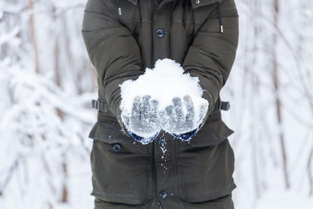 Winterferien, weihnachten und menschenkonzept - nahaufnahme einer frau mit schneeball im freien