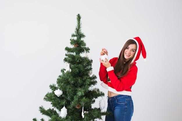 Winterferien-, weihnachts- und personenkonzept - glückliche junge frau gekleidet im weihnachtsmannkostüm, das weihnachtsbaum in weiß den raum mit kopienraum verziert