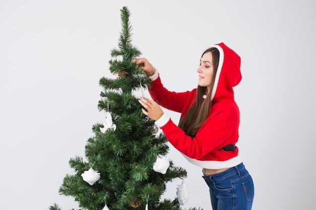 Winterferien-, weihnachts- und personenkonzept - porträt der schönen jungen frau in der weihnachtsmütze, die weihnachtsbaum zu hause im weißen raum verziert