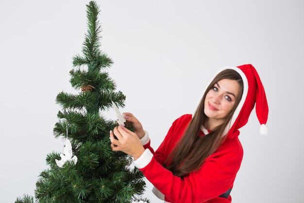 Winterferien-, weihnachts- und personenkonzept - porträt der schönen jungen frau in der weihnachtsmütze, die weihnachtsbaum zu hause verziert