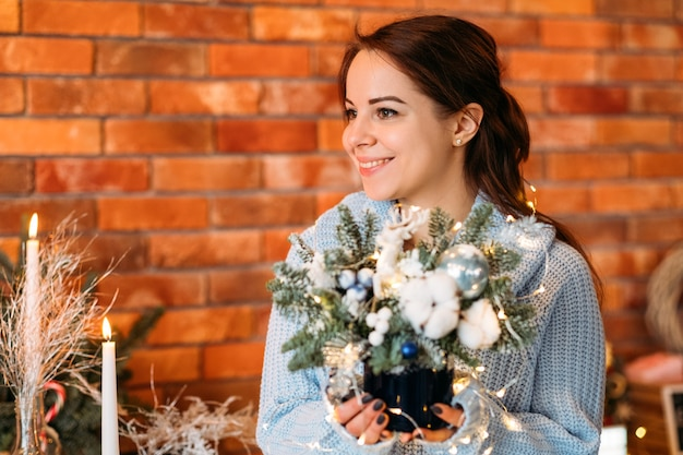 Winterferiengeschenk. porträt der glücklichen dame, die tannenbaumanordnung hält.