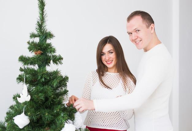 Winterferienkonzept - glückliches liebespaar, das weihnachtsbaum im zimmer schmückt.