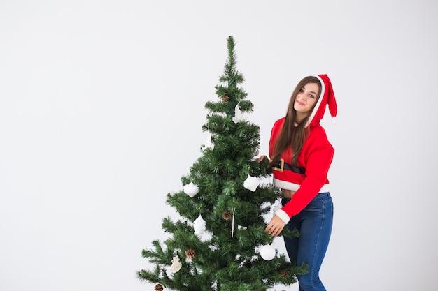 Winterferienweihnachten und leutekonzept schöne junge frau, die einen weihnachtsbaum in weiß schmückt