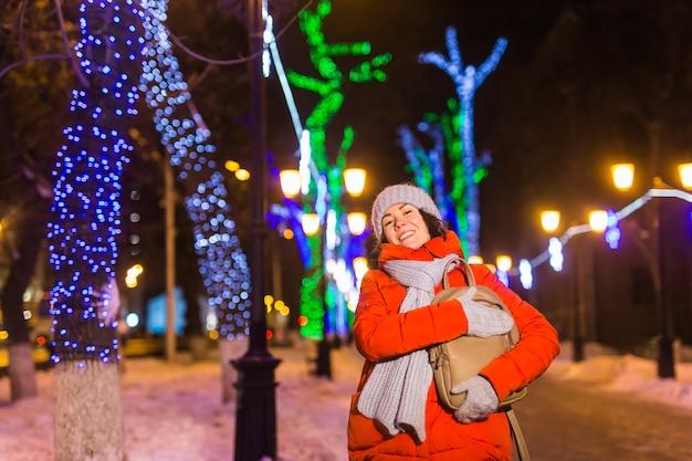 Winterferienzeit. weihnachten, neujahrskonzept. lustige glückliche frau verbringen zeit damit, spaß in der nähe von beleuchteten und dekorierten schaufenstern auf der stadtstraße zu haben.