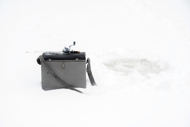 Winterfischen auf eis. wackelnder köder in einem eisloch.