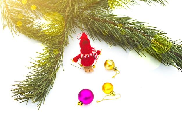 Winterfoto mit weihnachtsschmuck für kiefer. gestricktes schneemann-spielzeugmädchen, das auf dem ski im wald steht. frohe feiertage verziert postkarte. verschneites wetter.